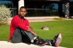 Homem novo que senta-se ao ar livre foto de stock