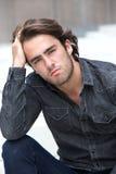 Homem novo que senta-se com mão no cabelo Fotografia de Stock Royalty Free
