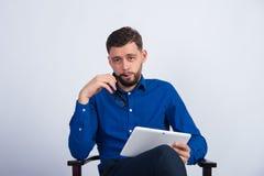 Homem novo que senta-se com uma tabuleta à disposição Fotografia de Stock Royalty Free