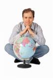 Homem novo que senta-se dentro atrás do globo Imagens de Stock