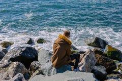 Homem novo que senta-se em rochas e que olha no Mar Negro Fotografia de Stock Royalty Free