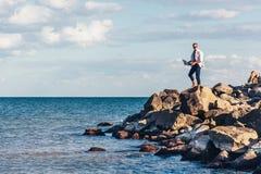 Homem novo que senta-se em um anúncio da rocha usando o portátil Foto de Stock