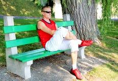 Homem novo que senta-se em um banco de parque Foto de Stock Royalty Free
