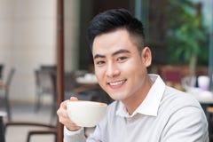 Homem novo que senta-se em um café em uma ruptura de café Imagens de Stock Royalty Free