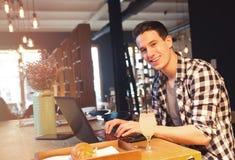 Homem novo que senta-se em um café, usando um portátil Fotografia de Stock Royalty Free