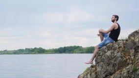 Homem novo que senta-se em um penhasco da rocha acima de um lago rural Menino de país Homem novo só video estoque