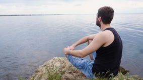 Homem novo que senta-se em um penhasco da rocha acima de um lago rural Menino de país Homem novo só filme
