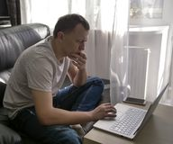 Homem novo que senta-se em um portátil em casa pela janela imagem de stock