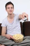 Homem novo que senta-se em um sofá e em uma tevê de observação Fotografia de Stock Royalty Free
