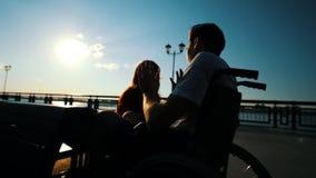 Homem novo que senta-se em uma cadeira de rodas e que fala a uma menina exterior filme