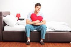 Homem novo que senta-se em uma cama Fotografia de Stock Royalty Free