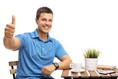 Homem novo que senta-se em uma mesa de centro e que faz um polegar acima do gestur Fotografia de Stock Royalty Free