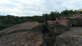 Homem novo que senta-se em uma rocha vídeos de arquivo