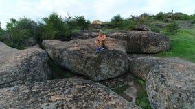 Homem novo que senta-se em uma rocha filme