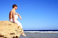 Homem novo que senta-se em uma rocha Imagens de Stock Royalty Free