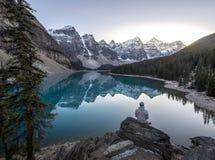 Homem novo que senta-se em uma rocha que negligencia o lago beautful da montanha Fotos de Stock