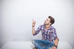 Homem novo que senta-se em uma tabela branca ao apontar acima Foto de Stock Royalty Free