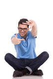 Homem novo que senta-se fazendo o frame Foto de Stock