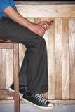 Homem novo que senta-se na barra com telefone móvel Imagem de Stock