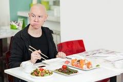 Homem novo que senta-se na barra de sushi, sorrindo Imagem de Stock