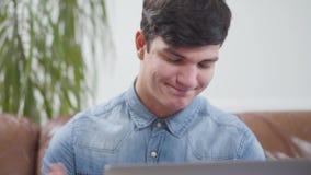 Homem novo que senta-se na frente do portátil em casa Retrato de um homem moreno que verifica a caixa postal Apego aos dispositiv filme