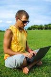 Homem novo que senta-se na grama e que trabalha com portátil Fotos de Stock