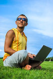 Homem novo que senta-se na grama e que trabalha com portátil Foto de Stock