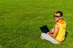 Homem novo que senta-se na grama e que trabalha com portátil Imagem de Stock Royalty Free