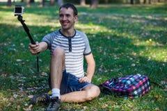 Homem novo que senta-se na grama e que toma o selfie em uma câmera da ação Imagens de Stock