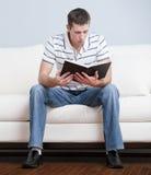 Homem novo que senta-se na leitura do sofá Fotografia de Stock