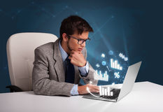 Homem novo que senta-se na mesa e que datilografa no portátil com diagramas e imagem de stock royalty free