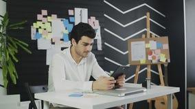 Homem novo que senta-se na mesa em seu escritório e que trabalha com alguns documentos e tablet pc video estoque
