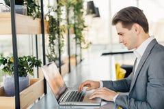 Homem novo que senta-se na mesa no escritório, trabalhando no computador portátil Imagens de Stock