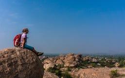 Homem novo que senta-se na montanha e que aprecia a vista após trekking Fotografia de Stock