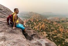 Homem novo que senta-se na montanha e que aprecia a vista após trekking Fotos de Stock