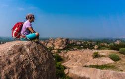 Homem novo que senta-se na montanha e que aprecia a vista após trekking Foto de Stock Royalty Free