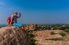 Homem novo que senta-se na montanha, enjoing a vista após trekking Imagem de Stock