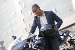 Homem novo que senta-se na motocicleta com o capacete que liga o motor excitado fotografia de stock royalty free