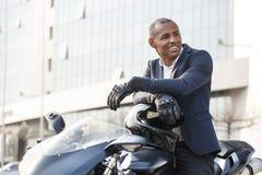 Homem novo que senta-se na motocicleta nas luvas do esporte que olham de lado felizes fotografia de stock