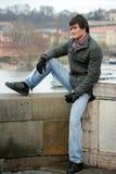 Homem novo que senta-se na parede Imagens de Stock