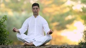 Homem novo que senta-se na parede e em meditar