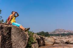 Homem novo que senta-se na pedra e que aprecia a vista após trekking Imagem de Stock