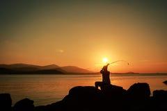 Homem novo que senta-se na pedra e que pesca no mar imagens de stock