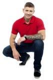 Homem novo que senta-se na posição squatting Fotografia de Stock Royalty Free