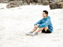 Homem novo que senta-se na praia no sportswear imagens de stock