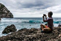 Homem novo que senta-se na rocha e que faz uma foto das ondas Fotografia de Stock Royalty Free