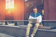Homem novo que senta-se na rua com portátil e Internet surfando fotografia de stock royalty free