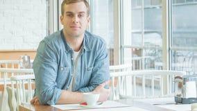 Homem novo que senta-se na tabela e no sorriso video estoque