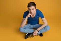 Homem novo que senta-se no assoalho Imagem de Stock