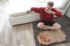 Homem novo que senta-se no assoalho em uma sala com uma caixa da pizza e dos canais de televisão de comutação no controlo a distâ imagem de stock